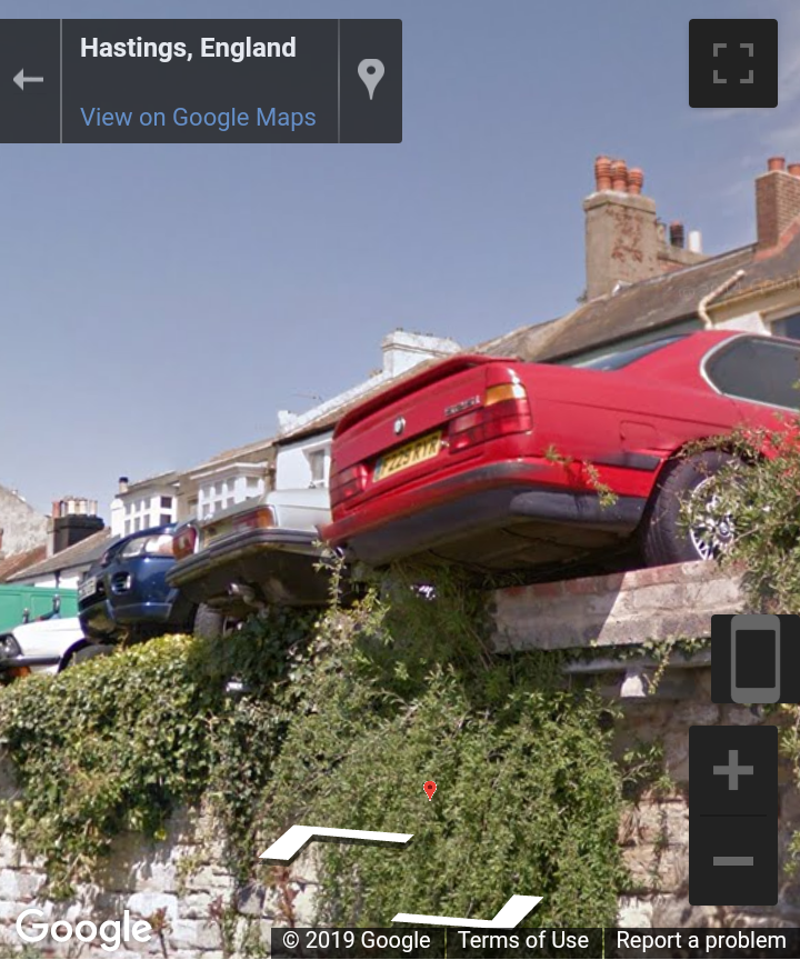 A car parked with its rear wheels on the edge of a steep drop